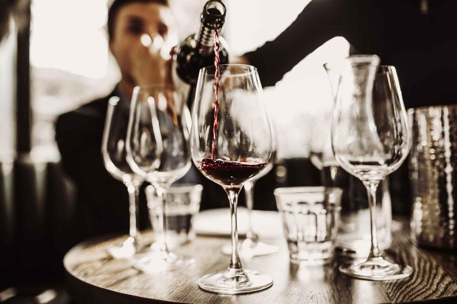 Servitris häller rött vin i ett glas då vänner upplever vinprovning i restaurang Västersalt på Bokenäset